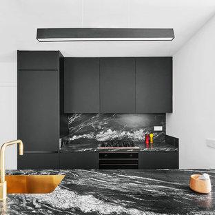 Imagen de cocina de galera, contemporánea, con fregadero bajoencimera, armarios con paneles lisos, puertas de armario negras, salpicadero negro y encimeras negras