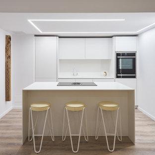 Foto de cocina lineal, actual, con armarios con paneles lisos, puertas de armario blancas, salpicadero blanco, electrodomésticos negros, una isla y encimeras blancas