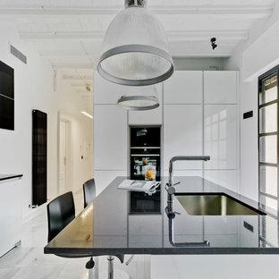 Diseño de cocina actual, cerrada, con armarios con paneles lisos, puertas de armario blancas, electrodomésticos negros, una isla, suelo blanco y encimeras negras