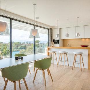 Ejemplo de cocina comedor lineal, contemporánea, con armarios con paneles lisos, puertas de armario blancas, encimera de madera, salpicadero de madera y una isla