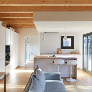 Modelo de cocina escandinava, abierta, con armarios con paneles lisos, puertas de armario blancas, encimera de madera, suelo de madera clara, una isla, suelo beige y encimeras beige