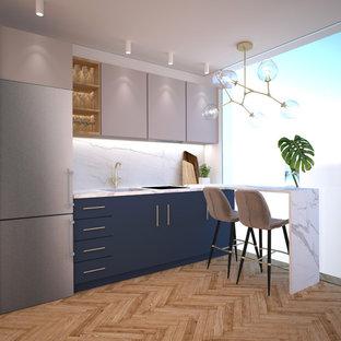 マドリードの小さいエクレクティックスタイルのおしゃれなキッチン (シングルシンク、フラットパネル扉のキャビネット、青いキャビネット、タイルカウンター、白いキッチンパネル、セラミックタイルのキッチンパネル、シルバーの調理設備、無垢フローリング、茶色い床、白いキッチンカウンター) の写真