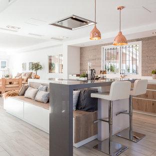 Modelo de cocina lineal, marinera, de tamaño medio, abierta, con armarios con paneles lisos, puertas de armario de madera clara, suelo de madera clara y una isla