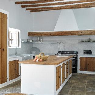Diseño de cocina en U, mediterránea, con fregadero sobremueble, armarios con paneles lisos, puertas de armario de madera oscura, salpicadero blanco, salpicadero de losas de piedra, electrodomésticos negros, una isla, suelo marrón y encimeras blancas