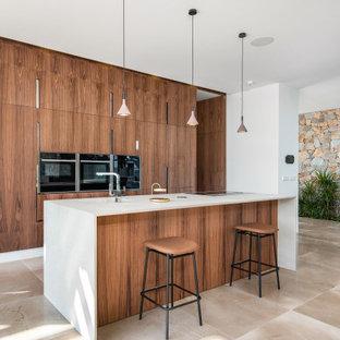 Imagen de cocina de galera, contemporánea, grande, con fregadero integrado, armarios con paneles lisos, puertas de armario de madera oscura, electrodomésticos con paneles, una isla, suelo beige y encimeras blancas