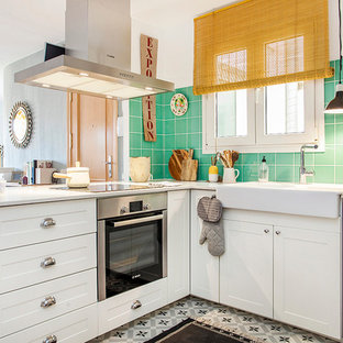 Photo of a mid-sized midcentury l-shaped open plan kitchen in Barcelona with a drop-in sink, recessed-panel cabinets, white cabinets, green splashback, cement tile splashback, stainless steel appliances, ceramic floors and no island.