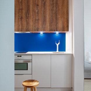 Diseño de cocina nórdica, pequeña, con fregadero bajoencimera, puertas de armario de madera oscura, salpicadero azul, electrodomésticos blancos, suelo de madera clara y encimeras blancas