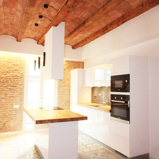 Mid-sized modern single-wall open plan kitchen in Barcelona with an undermount sink, white cabinets, wood benchtops, black splashback, slate splashback, panelled appliances, cement tiles, with island, multi-coloured floor, flat-panel cabinets and brown benchtop.