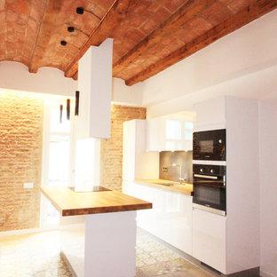 Offene, Einzeilige, Mittelgroße Moderne Küche mit Unterbauwaschbecken, weißen Schränken, Arbeitsplatte aus Holz, Küchenrückwand in Schwarz, Rückwand aus Schiefer, Elektrogeräten mit Frontblende, Zementfliesen, Kücheninsel, buntem Boden, flächenbündigen Schrankfronten und brauner Arbeitsplatte in Barcelona