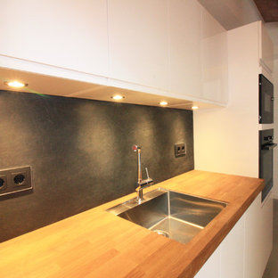 Photo of a mid-sized modern single-wall open plan kitchen in Barcelona with an undermount sink, recessed-panel cabinets, white cabinets, wood benchtops, black splashback, slate splashback, stainless steel appliances, cement tiles, with island and multi-coloured floor.
