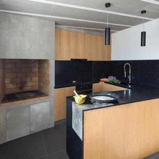 Diseño de cocina comedor en U, urbana, con armarios con paneles lisos, encimeras negras, puertas de armario de madera clara, salpicadero negro, electrodomésticos negros, península y suelo gris