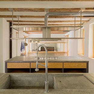 Imagen de cocina lineal, industrial, grande, con armarios abiertos, puertas de armario de madera oscura, encimera de piedra caliza y una isla