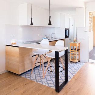 他の地域の小さい地中海スタイルのおしゃれなキッチン (フラットパネル扉のキャビネット、淡色木目調キャビネット、クオーツストーンカウンター、白いキッチンパネル、青い床、白いキッチンカウンター) の写真