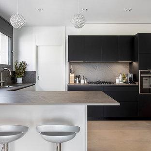 Modelo de cocina contemporánea con fregadero bajoencimera, armarios con paneles lisos, puertas de armario negras, salpicadero verde, salpicadero de losas de piedra, electrodomésticos negros, suelo de cemento, península, suelo gris y encimeras grises