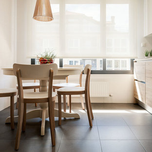 Mid-sized modern single-wall eat-in kitchen in Bilbao with flat-panel cabinets, white splashback, panelled appliances, ceramic floors, a drop-in sink, light wood cabinets, solid surface benchtops and mirror splashback.