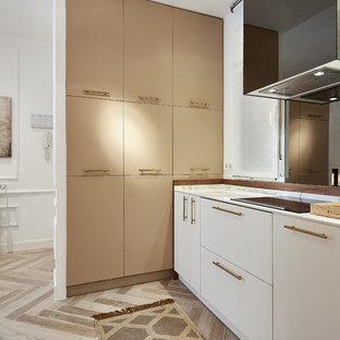 Imagen de cocina lineal, actual, abierta, sin isla, con fregadero bajoencimera, armarios con paneles lisos, puertas de armario blancas, salpicadero metalizado, salpicadero con efecto espejo, suelo beige y encimeras blancas