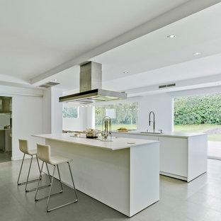 Ejemplo de cocina de galera, moderna, grande, abierta, con armarios con paneles lisos, puertas de armario blancas, dos o más islas, suelo gris y encimeras blancas