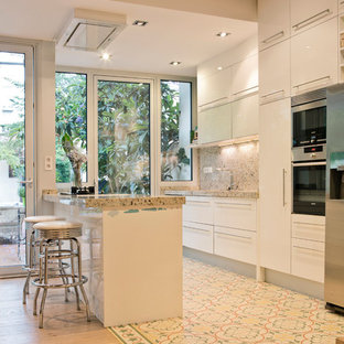 Inspiration for a contemporary single-wall open plan kitchen in Barcelona with flat-panel cabinets, white cabinets, stainless steel appliances, a peninsula, ceramic floors, beige splashback, stone slab splashback, multi-coloured floor and beige benchtop.