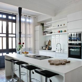 Modelo de cocina nórdica con encimera de cuarzo compacto, salpicadero de vidrio, encimeras blancas, armarios con paneles lisos, puertas de armario blancas, salpicadero blanco y una isla