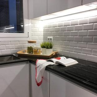 Modelo de cocina clásica renovada con fregadero bajoencimera, armarios con paneles lisos, puertas de armario blancas, encimera de granito, electrodomésticos de acero inoxidable, suelo de terrazo, salpicadero blanco y salpicadero de azulejos tipo metro