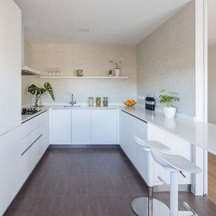 Imagen de cocina comedor en U, contemporánea, con fregadero bajoencimera, armarios con paneles lisos, puertas de armario blancas, salpicadero beige, electrodomésticos con paneles, península, suelo marrón y encimeras blancas
