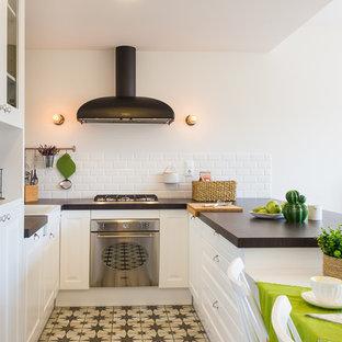 Ejemplo de cocina en U, campestre, de tamaño medio, abierta, con armarios con paneles empotrados, puertas de armario blancas y península