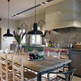 Modelo de cocina comedor lineal, de estilo de casa de campo, grande, con armarios con paneles lisos, puertas de armario grises, salpicadero verde, encimeras grises, salpicadero de losas de piedra, electrodomésticos de acero inoxidable, suelo de cemento y suelo gris