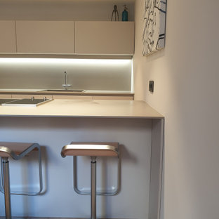 Large modern single-wall eat-in kitchen in Valencia with a farmhouse sink, flat-panel cabinets, grey cabinets, limestone benchtops, grey splashback, limestone splashback, black appliances, laminate floors, a peninsula, brown floor and grey benchtop.