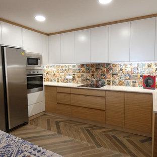 Ejemplo de cocina en U, moderna, de tamaño medio, cerrada, con fregadero encastrado, armarios con paneles lisos, puertas de armario de madera clara, encimera de cuarzo compacto, salpicadero con mosaicos de azulejos, electrodomésticos de acero inoxidable, suelo de terrazo y suelo gris