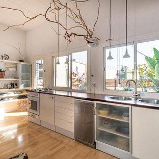 Foto på ett stort eklektiskt brun linjärt kök med öppen planlösning, med en dubbel diskho, släta luckor, vita skåp, träbänkskiva, stänkskydd med metallisk yta, stänkskydd i metallkakel, rostfria vitvaror, mellanmörkt trägolv och brunt golv