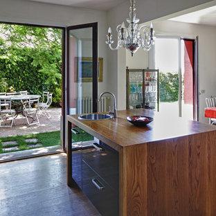 バルセロナの大きいエクレクティックスタイルのおしゃれなキッチン (シングルシンク、フラットパネル扉のキャビネット、黒いキャビネット、木材カウンター、白いキッチンパネル、大理石のキッチンパネル、パネルと同色の調理設備、無垢フローリング、茶色い床、茶色いキッチンカウンター) の写真