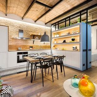 Diseño de cocina comedor en L, mediterránea, con armarios abiertos, puertas de armario blancas, salpicadero beige, electrodomésticos negros, suelo de madera clara y suelo beige