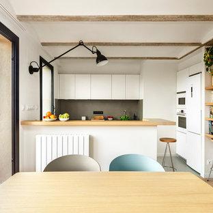 Diseño de cocina de galera, contemporánea, de tamaño medio, abierta, con armarios con paneles lisos, puertas de armario blancas, encimera de madera, salpicadero verde, electrodomésticos blancos y península