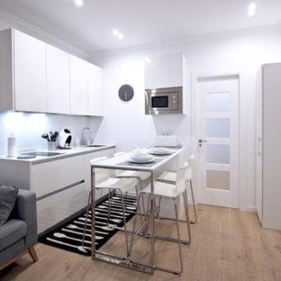 Ejemplo de cocina escandinava, pequeña, abierta, con armarios con paneles lisos, puertas de armario blancas, salpicadero blanco, electrodomésticos de acero inoxidable, península, encimeras blancas, fregadero bajoencimera y suelo de madera clara