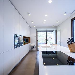 Diseño de cocina comedor lineal, actual, grande, con fregadero integrado, armarios con paneles lisos, puertas de armario blancas, una isla y encimeras blancas