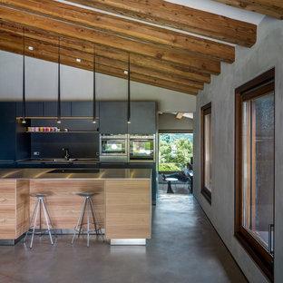 Réalisation d'une grand cuisine américaine parallèle design avec un placard à porte plane, des portes de placard noires, un plan de travail en inox, une crédence noire, un électroménager en acier inoxydable, béton au sol et un îlot central.