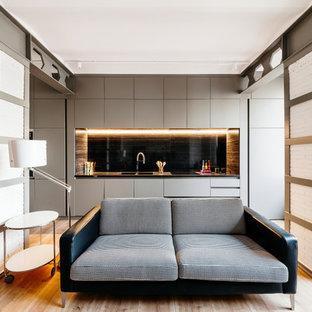 Imagen de cocina lineal, actual, de tamaño medio, abierta, sin isla, con armarios con paneles lisos, puertas de armario grises, salpicadero negro, suelo de madera en tonos medios y encimeras negras