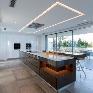 Diseño de cocina contemporánea, extra grande, con armarios con paneles lisos, puertas de armario marrones, una isla, encimeras blancas, fregadero de un seno y suelo beige