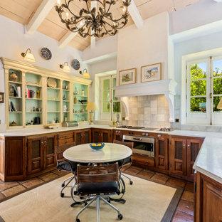 Diseño de cocina comedor en U, mediterránea, sin isla, con armarios con paneles con relieve, puertas de armario de madera en tonos medios, salpicadero verde, electrodomésticos de acero inoxidable, suelo marrón y encimeras blancas