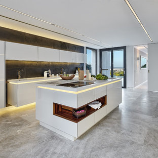 Design ideas for a large contemporary galley kitchen in Palma de Mallorca with an integrated sink, flat-panel cabinets, white cabinets, solid surface benchtops, black splashback, slate splashback, stainless steel appliances, limestone floors, with island, white benchtop and grey floor.