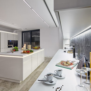 Inspiration for a large modern eat-in kitchen in Palma de Mallorca with an integrated sink, flat-panel cabinets, white cabinets, solid surface benchtops, black splashback, slate splashback, stainless steel appliances, limestone floors, with island, beige floor and white benchtop.