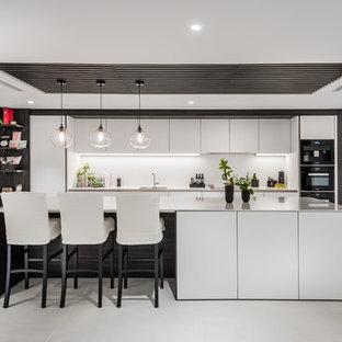 Foto de cocina de galera, actual, con fregadero bajoencimera, armarios con paneles lisos, puertas de armario blancas, electrodomésticos negros, una isla, suelo gris y encimeras blancas