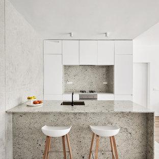 Modelo de cocina moderna con fregadero bajoencimera, armarios con paneles lisos, puertas de armario blancas, salpicadero verde, electrodomésticos de acero inoxidable, península y suelo gris