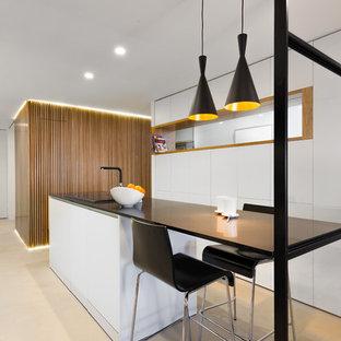 Diseño de cocina contemporánea, de tamaño medio, con armarios con paneles lisos, puertas de armario blancas, encimera de cuarzo compacto, suelo de cemento, una isla, encimeras negras y suelo beige
