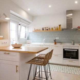 Modelo de cocina nórdica con fregadero encastrado, armarios estilo shaker, puertas de armario blancas, salpicadero azul, suelo de madera clara, península, suelo beige y encimeras blancas