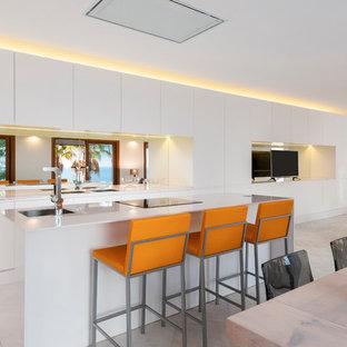Imagen de cocina de galera, contemporánea, grande, abierta, con armarios con paneles lisos, puertas de armario blancas, electrodomésticos con paneles y una isla