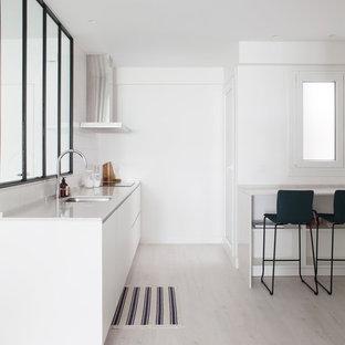 Imagen de cocina lineal, minimalista, abierta, sin isla, con fregadero bajoencimera, puertas de armario blancas, encimeras blancas, armarios con paneles lisos, salpicadero blanco, electrodomésticos con paneles, suelo de madera clara y suelo beige