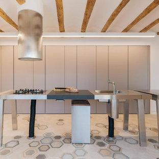 Modelo de cocina en L, mediterránea, con fregadero integrado, armarios con paneles lisos, puertas de armario grises, encimera de acero inoxidable, electrodomésticos de acero inoxidable, una isla, suelo multicolor y encimeras grises