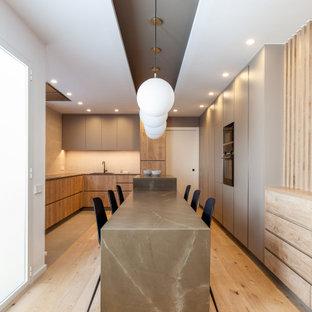Diseño de cocina en U, actual, grande, con fregadero encastrado, armarios con paneles lisos, puertas de armario de madera oscura, electrodomésticos con paneles, dos o más islas, suelo beige y encimeras grises