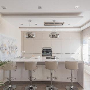 Imagen de cocina actual con fregadero de doble seno, armarios con paneles lisos, puertas de armario beige, electrodomésticos de acero inoxidable, suelo de madera clara, península, suelo beige y encimeras blancas